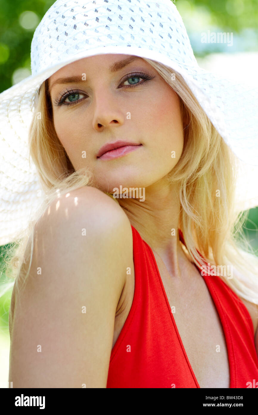 Vertical image of pretty young lady in elegant hat looking aside - Stock Image