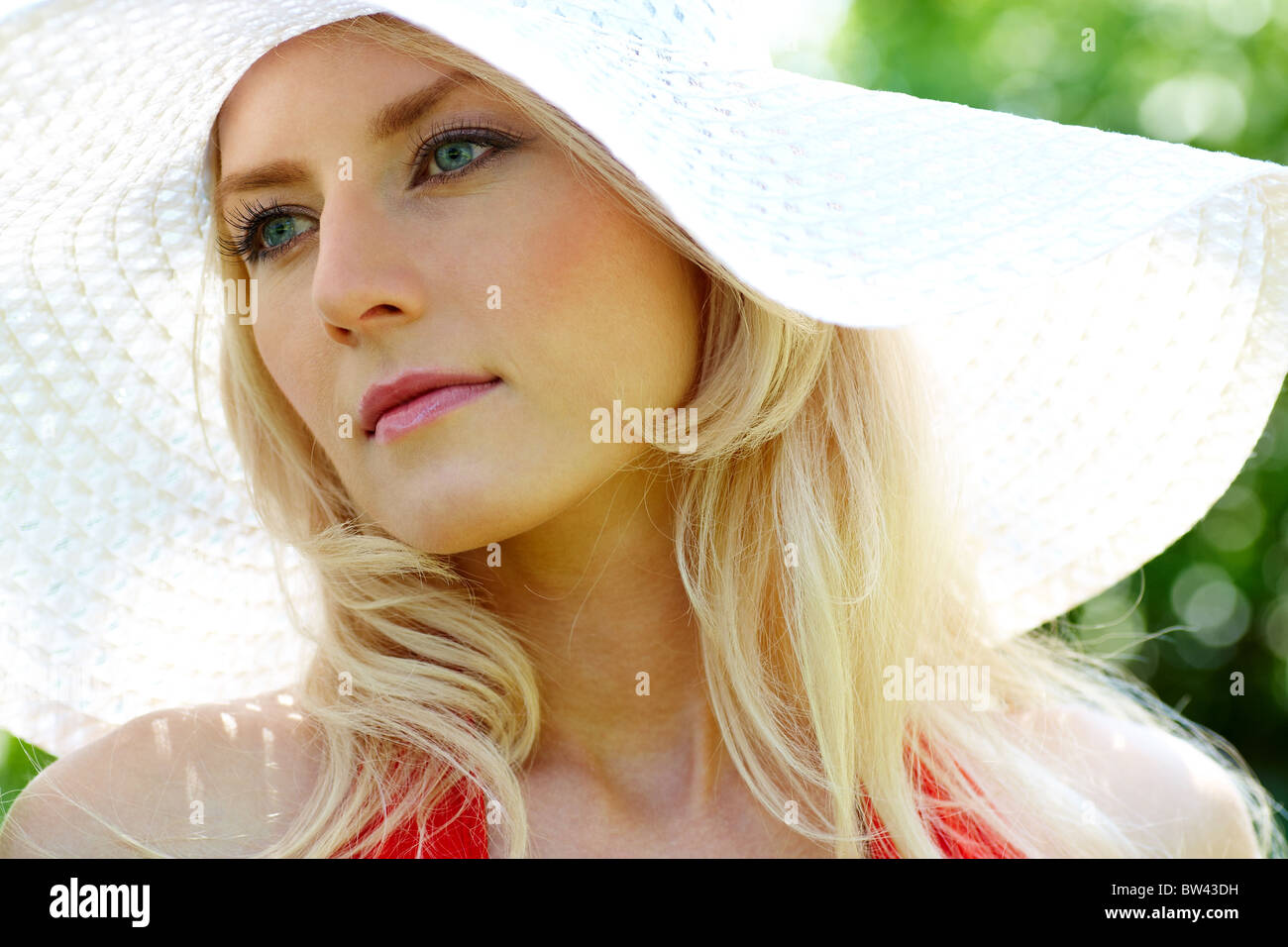 Pretty young lady in elegant hat looking aside at summer - Stock Image