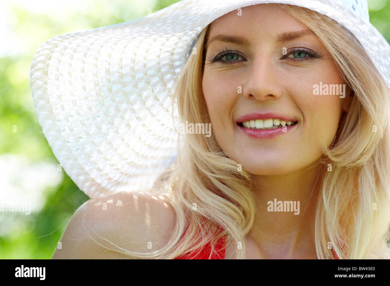 Pretty young lady in elegant hat smiling while looking at camera - Stock Image