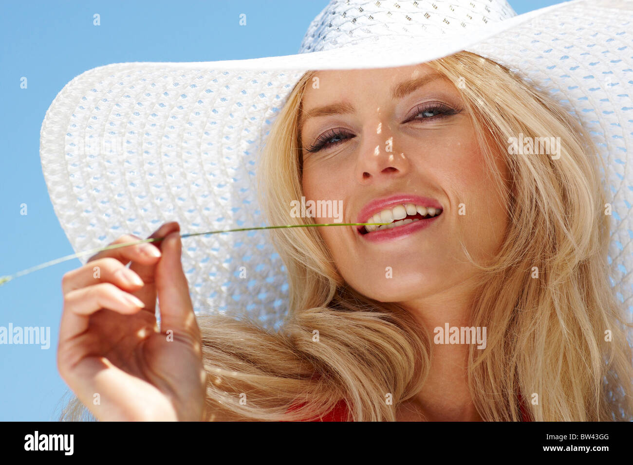 Pretty blonde in elegant hat looking at camera against blue sky Stock Photo