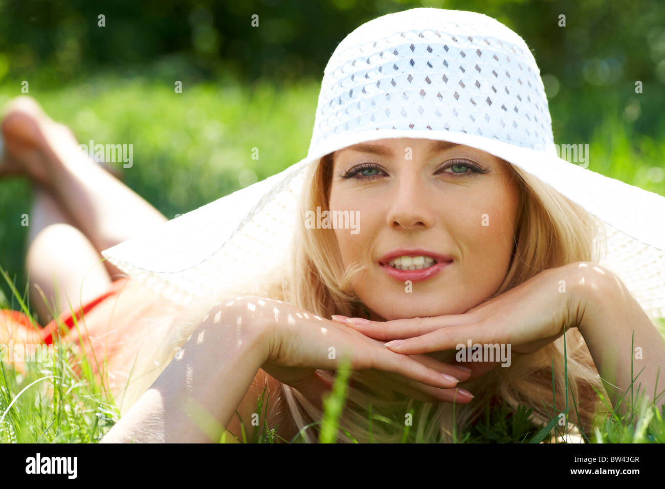 Pretty young lady in elegant hat relaxing in green grass Stock Photo