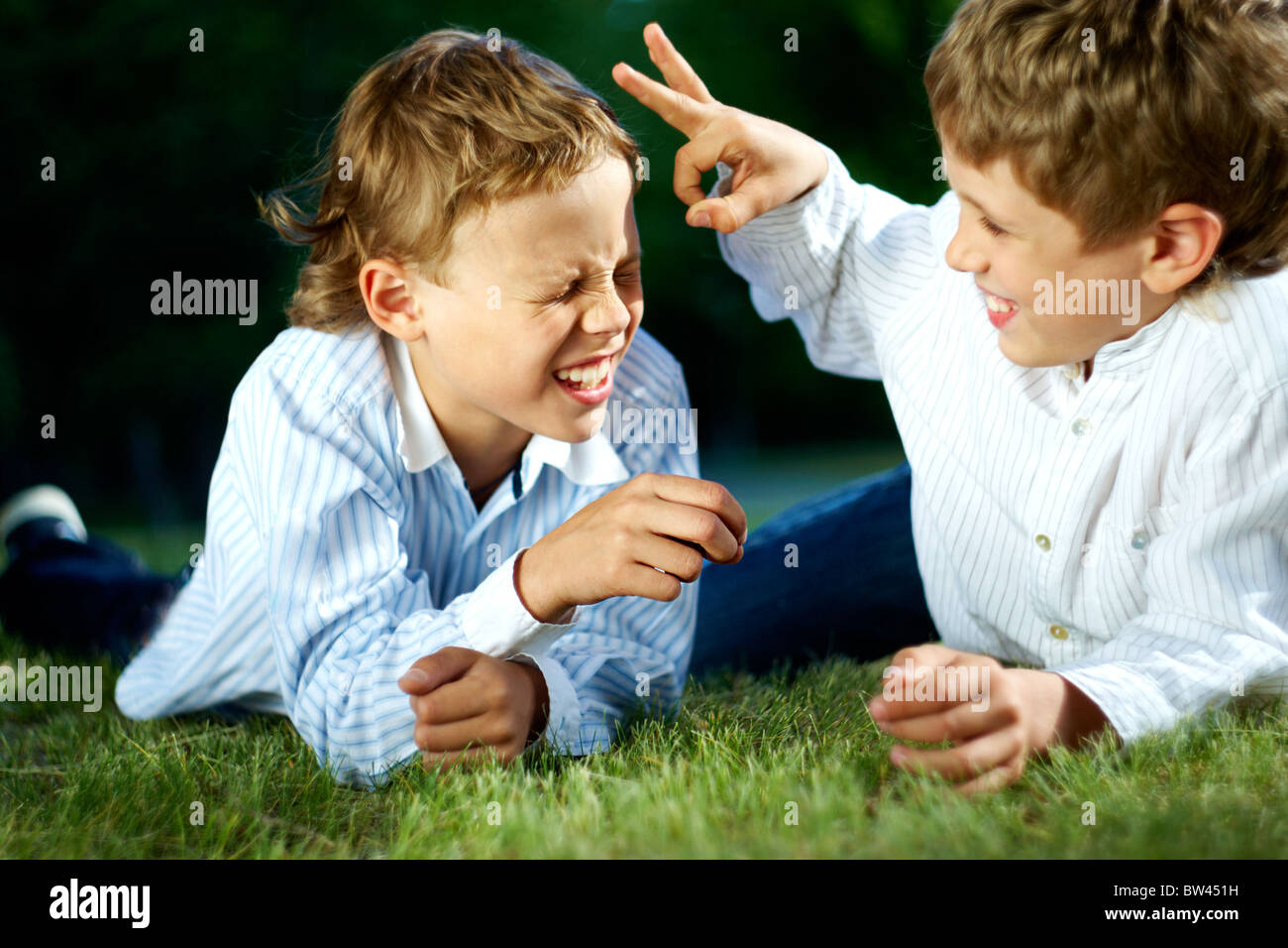 Portrait of happy boys playing jokes on grass in park - Stock Image
