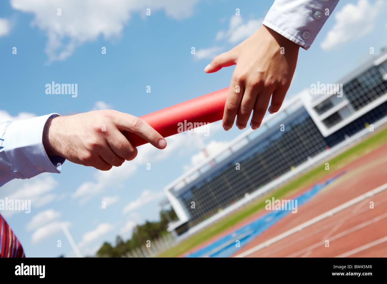 Photo of business people hands passing baton during marathon - Stock Image