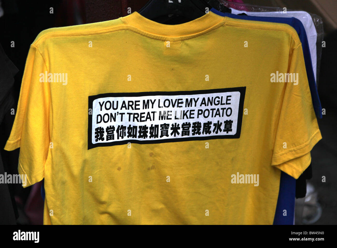 An amusing T-shirt with bad translation on display at the market in Stanley, Hong Kong, China. - Stock Image