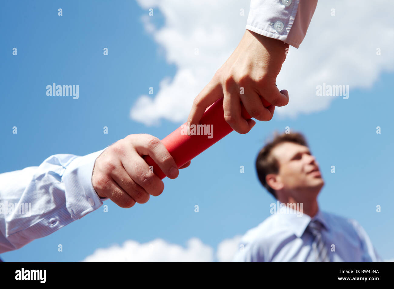 Photo of business people hands passing baton during race - Stock Image