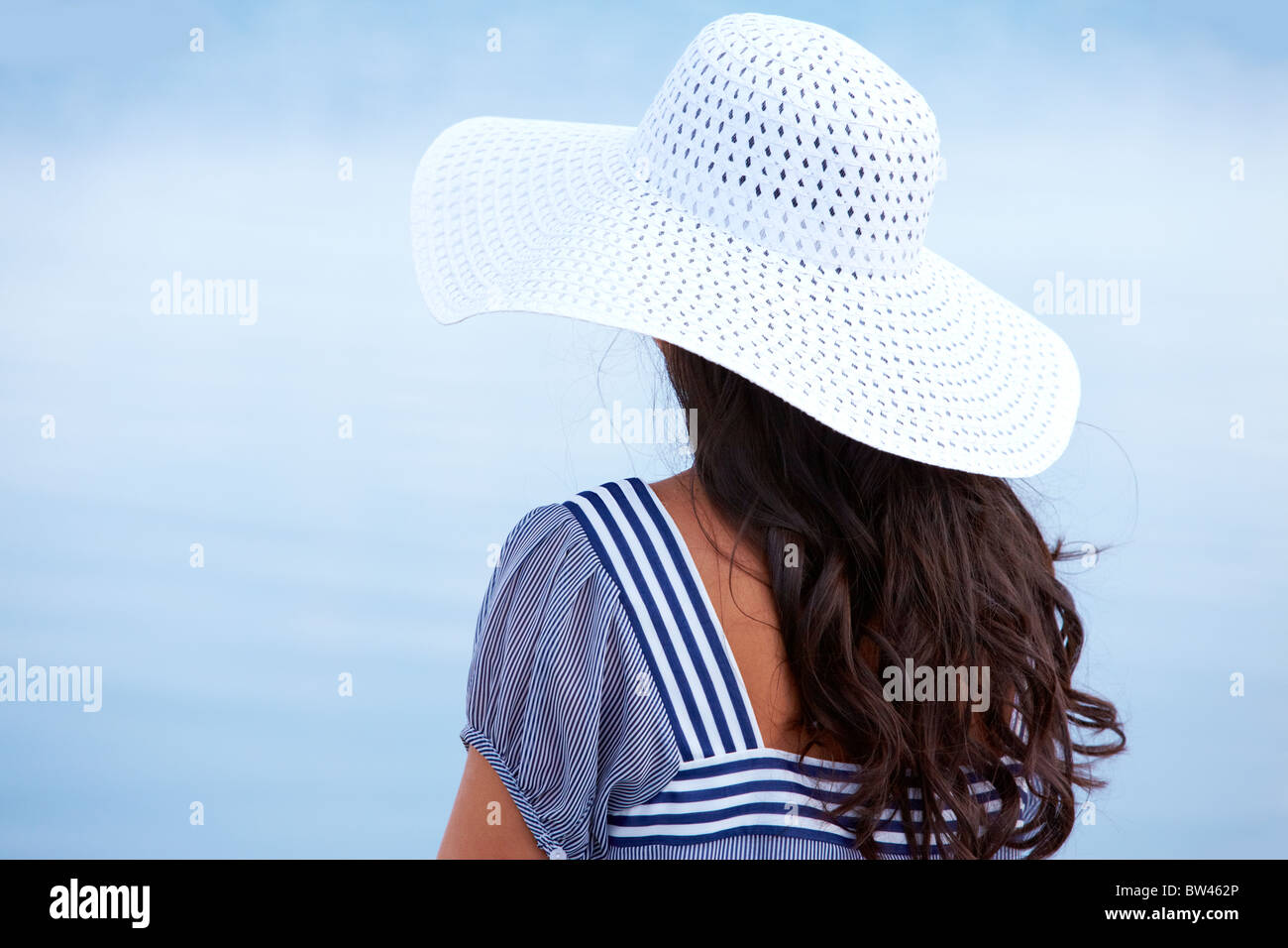 Rear view of pretty young lady in hat outdoors Stock Photo