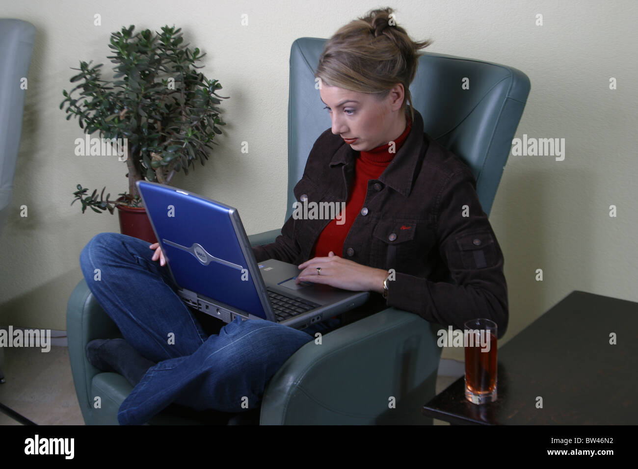 White woman corporate on chair with laptop - Stock Image