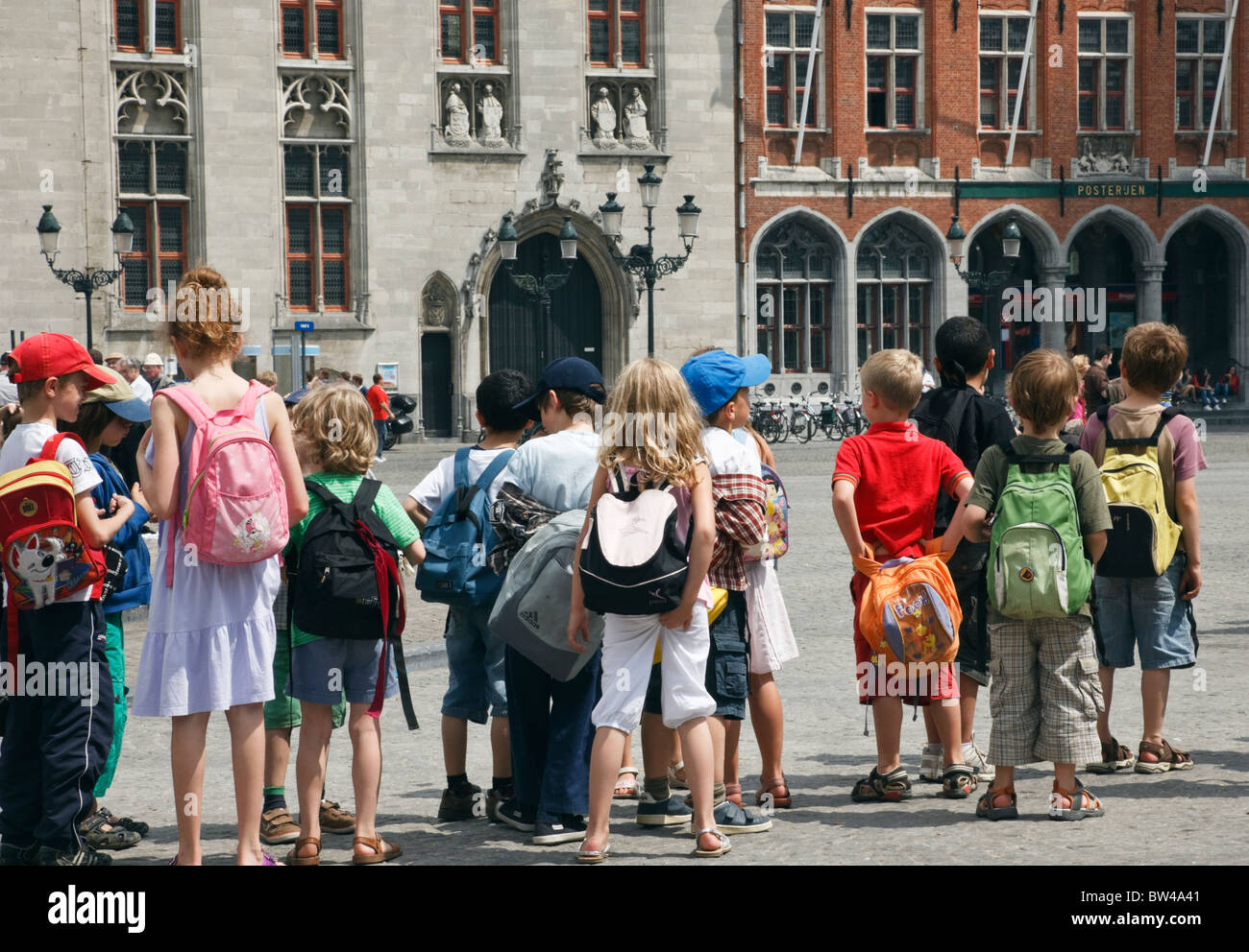 Markt, Bruges, Belgium, Europe. Group of children wearing rucksacks on a school trip to the historic city square - Stock Image
