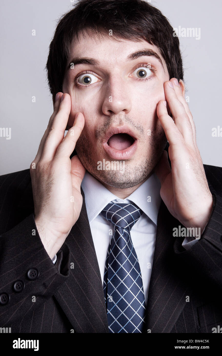 Funny portrait of amazed young business man - Stock Image