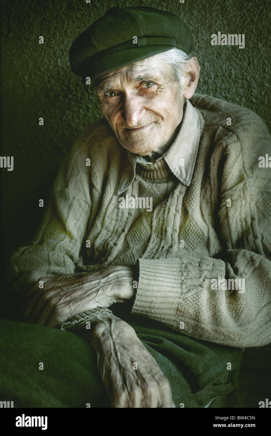 Artistic portrait of old senior man with wrinkled hands - Stock Image
