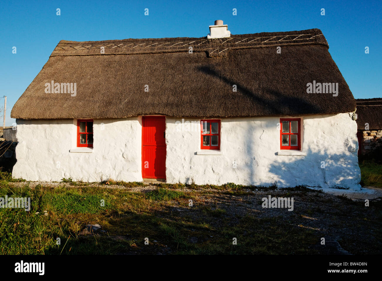 Thatched cottage with red door, near Rossaveel, Connemara, County Galway, Connaught, Ireland. - Stock Image