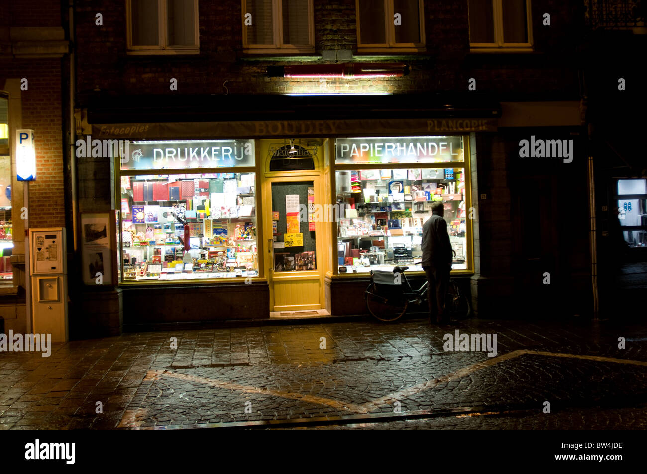 A man looks into the window of a shop of a wet and windy night in Ypres, Belgium - Stock Image