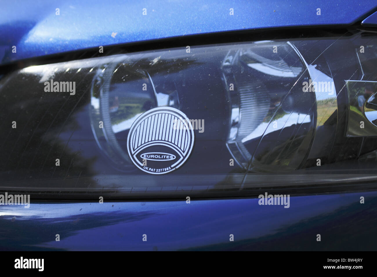 Headlight deflectors fitted to a UK car for driving on the right in Europe. - Stock Image