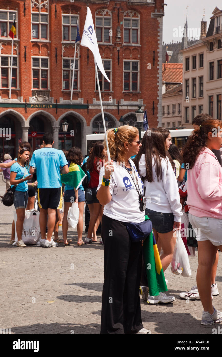 Markt, Bruges, Belgium, Europe. Tourists shopping tour guide with flag in the historic city - Stock Image