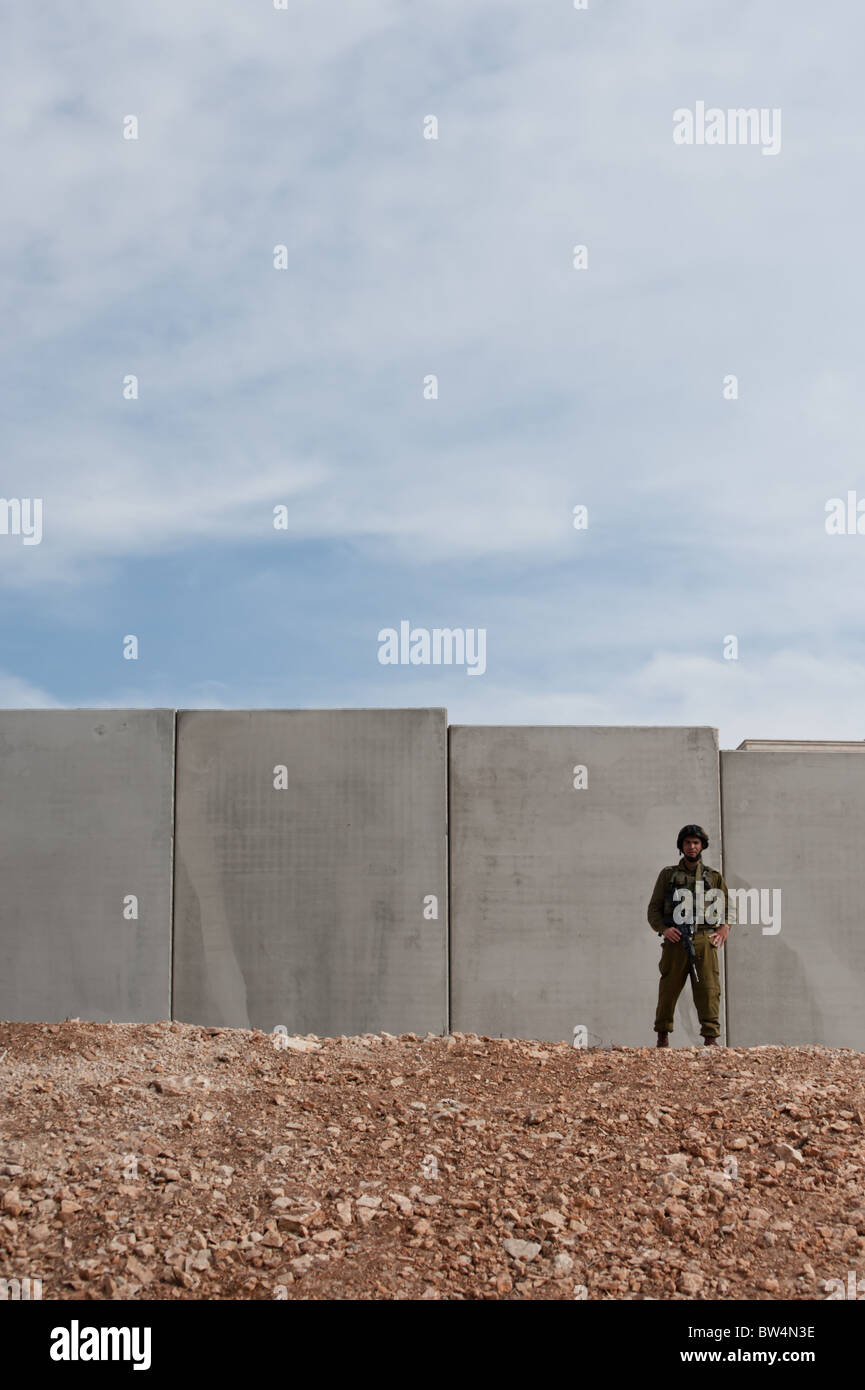 An Israeli soldier stand in front of the Israeli separation barrier which threatens to encircle the West Bank town - Stock Image