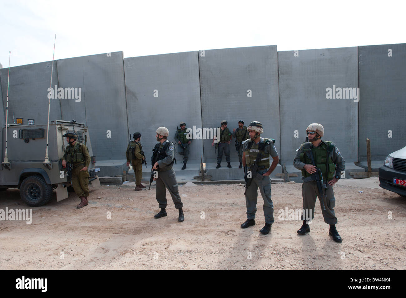 Israeli soldiers stand in front of the Israeli separation barrier which threatens to encircle the West Bank town - Stock Image