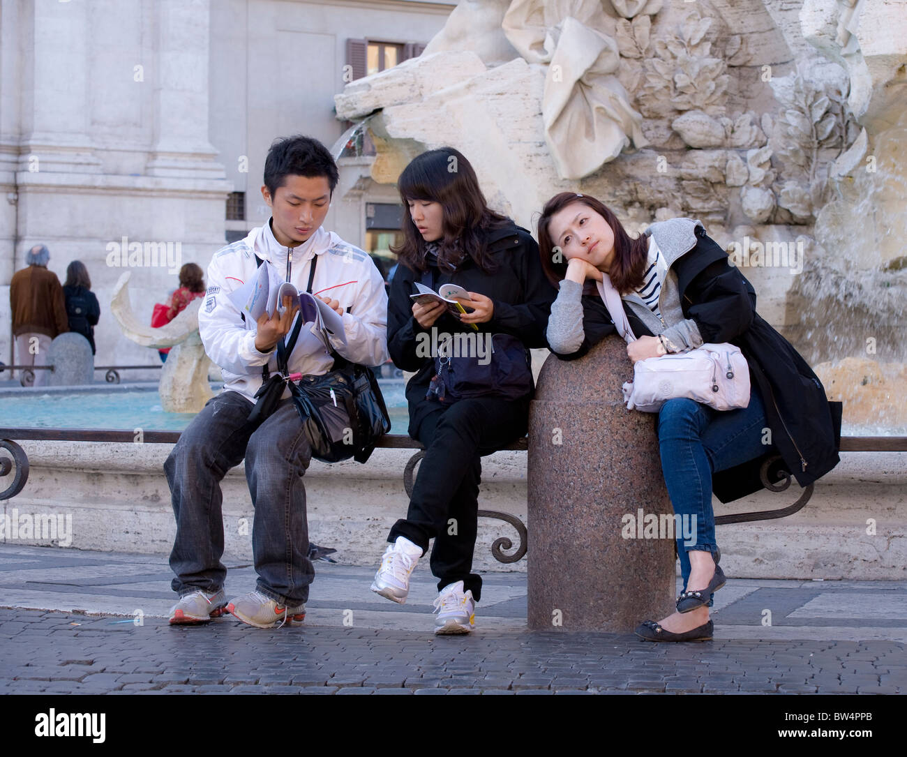 Young Japanese tourists taking a break at Piazza Navona in Rome. Stock Photo