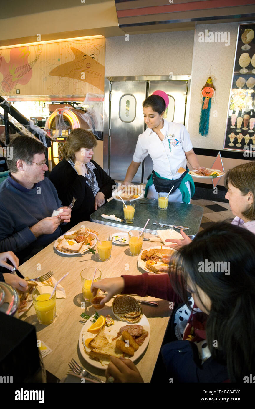 A waitress serving food to a family in Annettes Diner, Disneyland Paris village, France, Europe - Stock Image