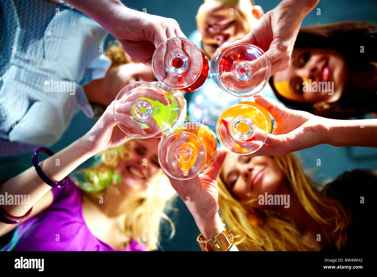 Below view of people clinking glasses with each other - Stock Image