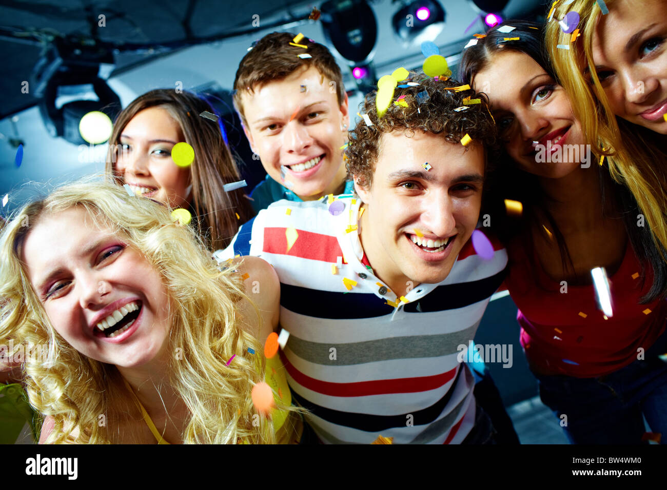 Portrait of happy glamorous friends in a night club - Stock Image