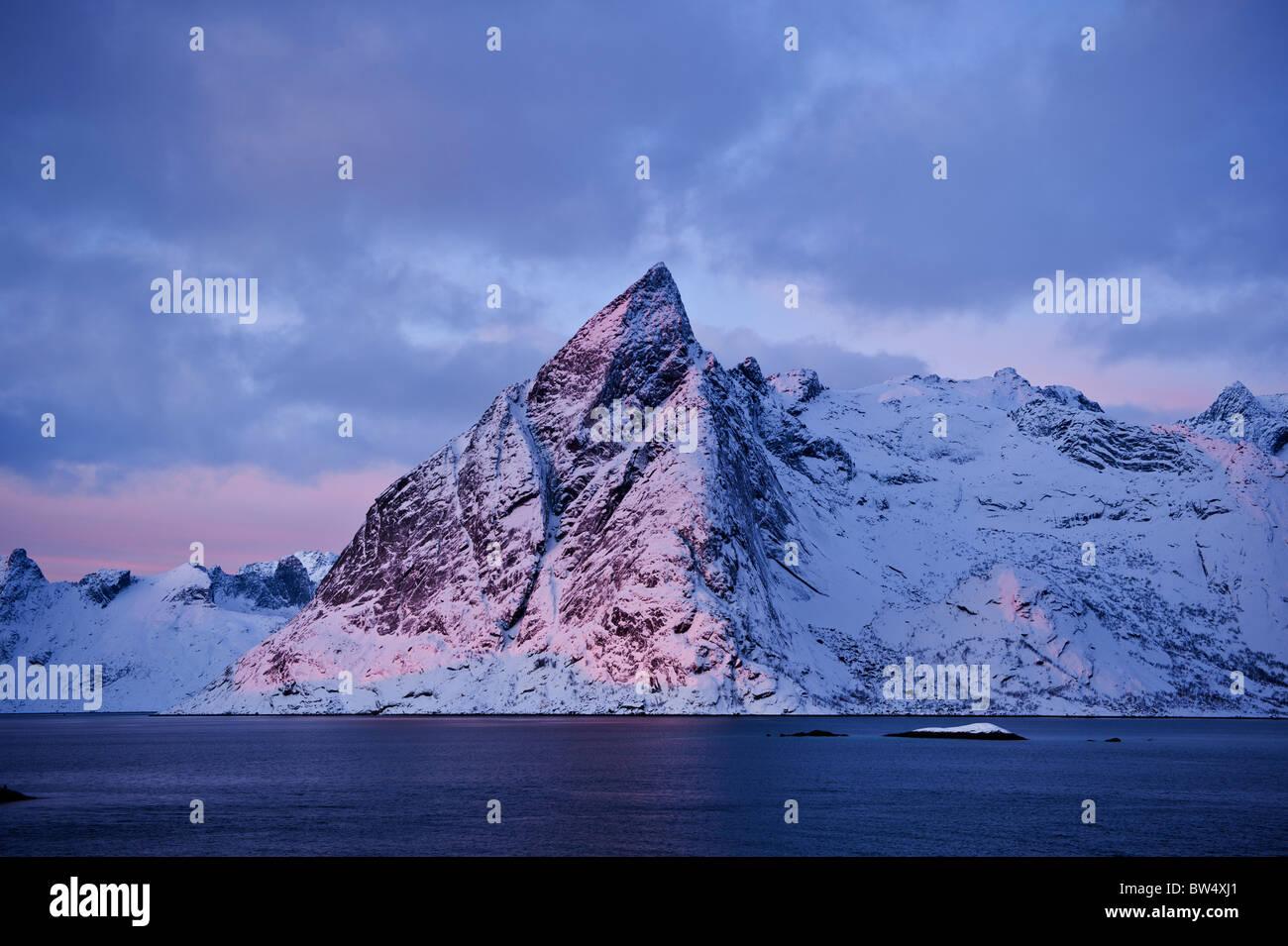 Olstinden mountain peak lit by January sun, Reine, Lofoten islands, Norway Stock Photo
