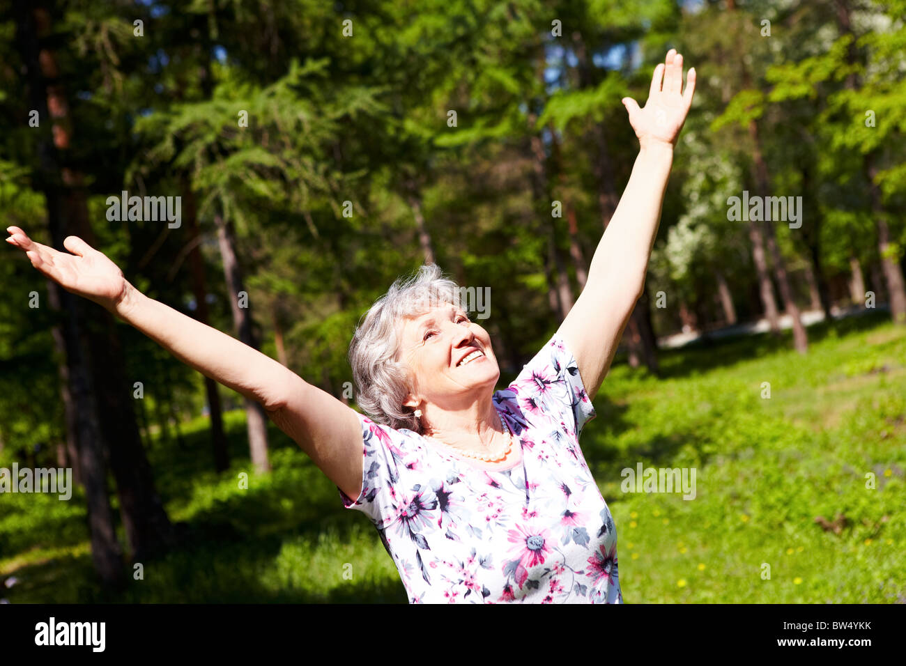 Portrait of aged woman with her arms raised in praise - Stock Image