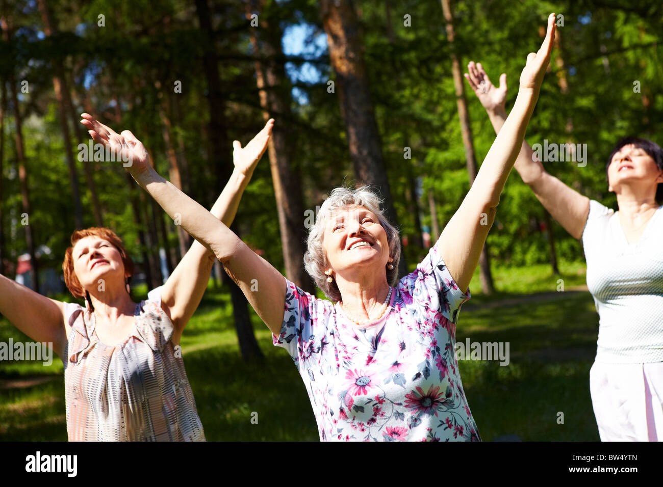Portrait of aged women with their arms raised in praise - Stock Image