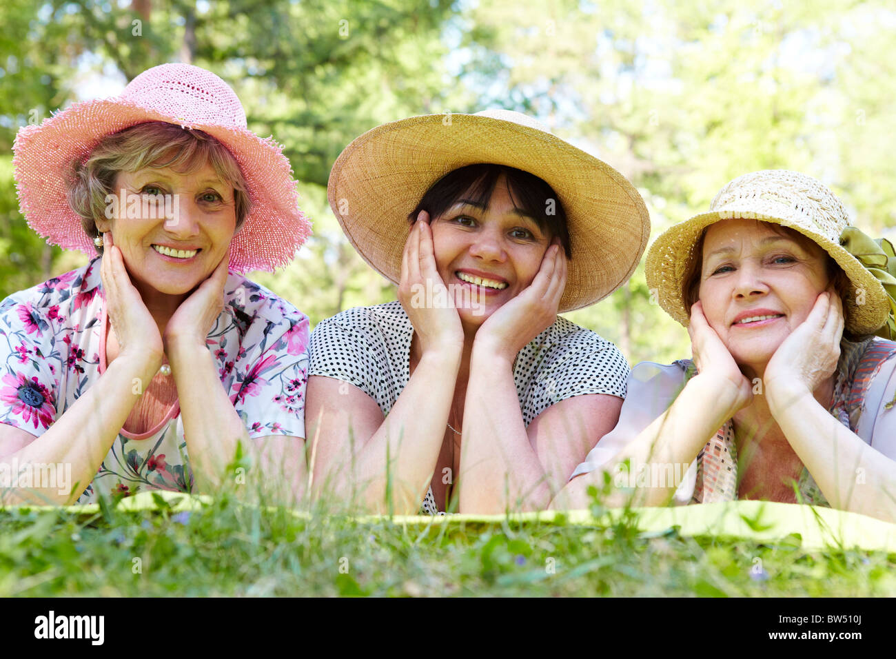 Portrait of three aged women in elegant hats resting on grass - Stock Image