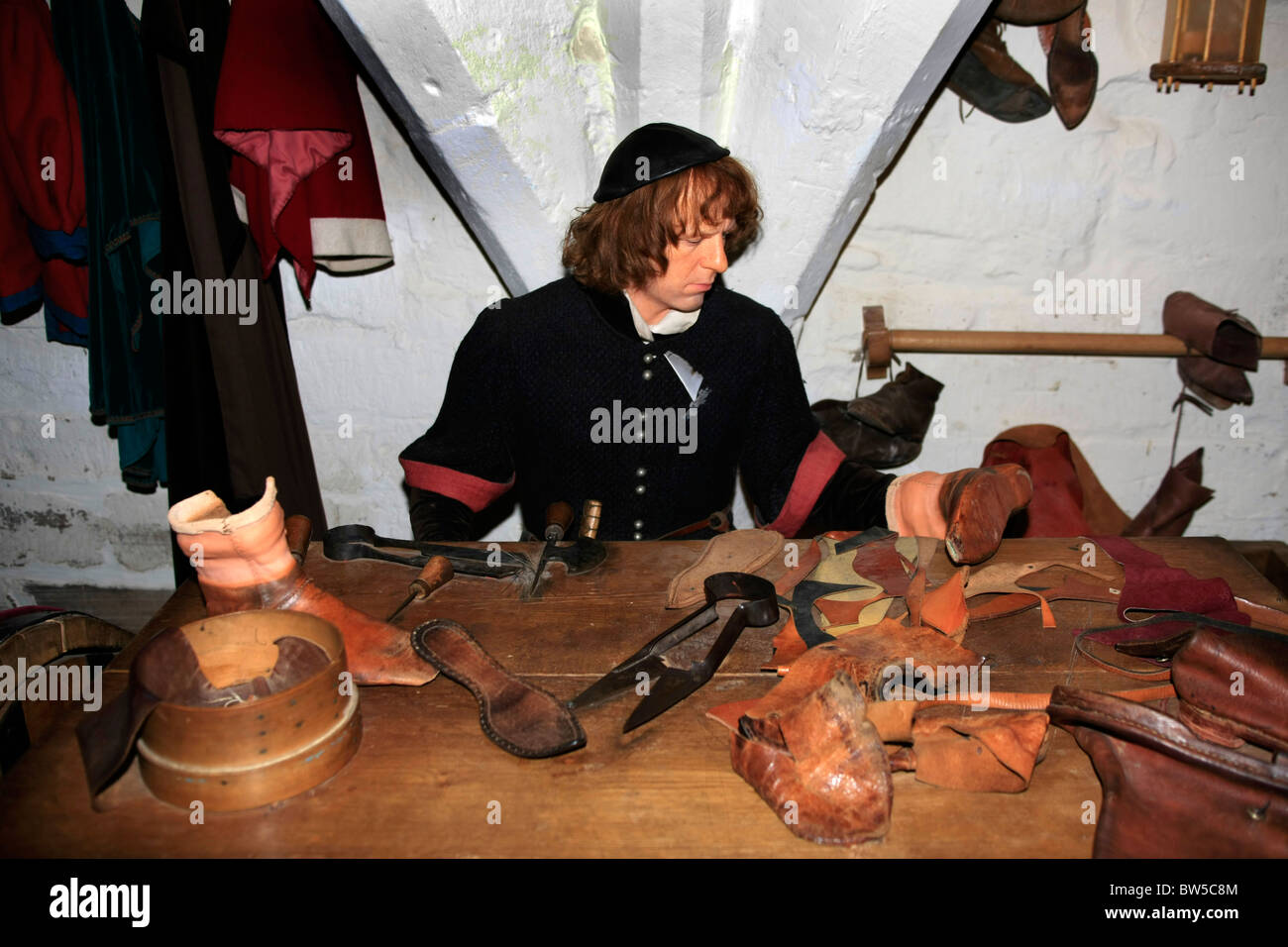A Leather worker at work in the Undercroft of Warwick Castle - Stock Image