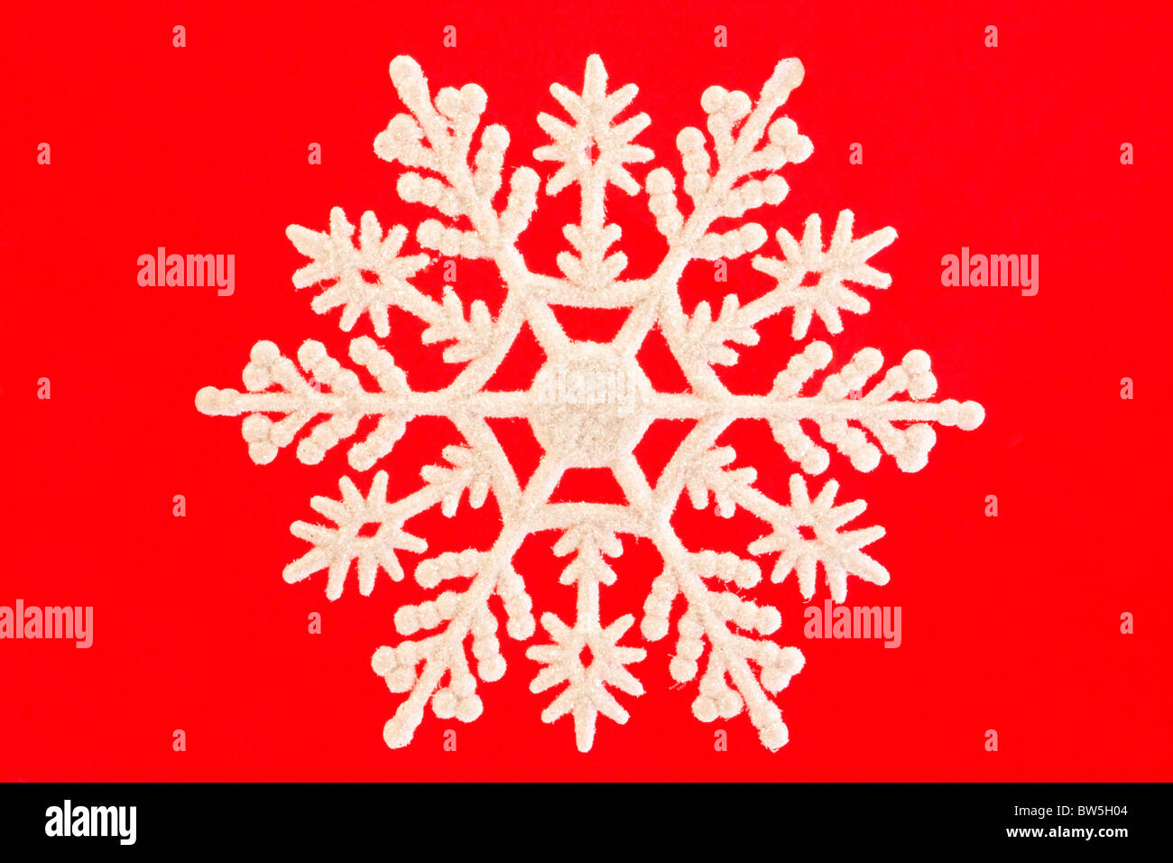 single white snowflake isolated over red - Stock Image