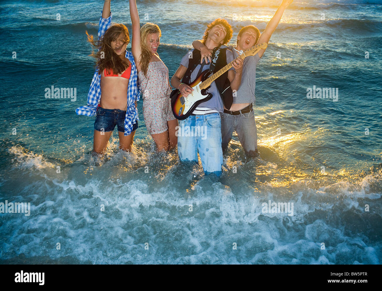 Young group sing with guitar in tide sea - Stock Image
