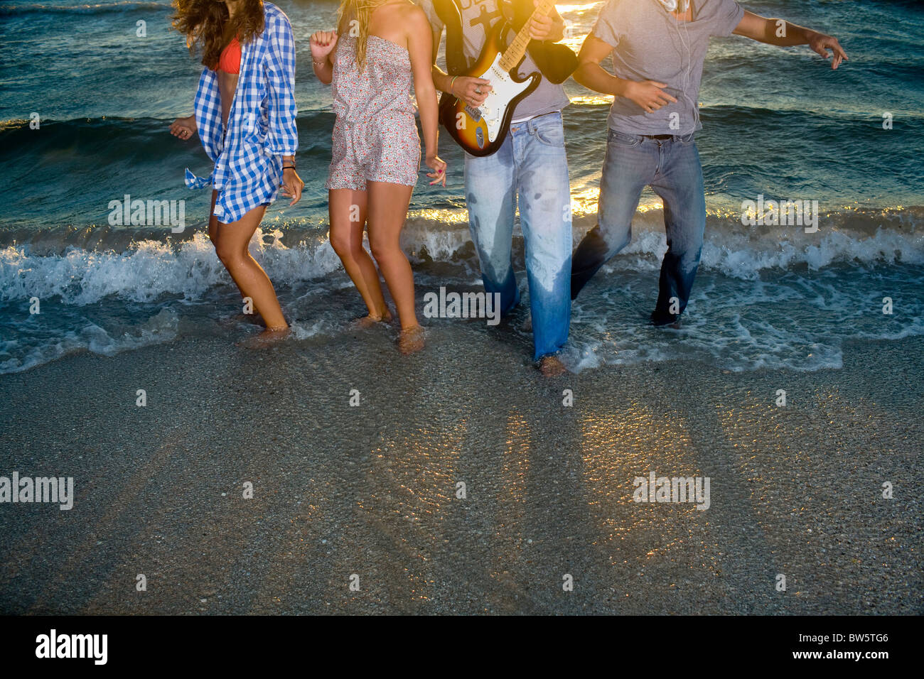 Group dance with guitar in beach tide - Stock Image
