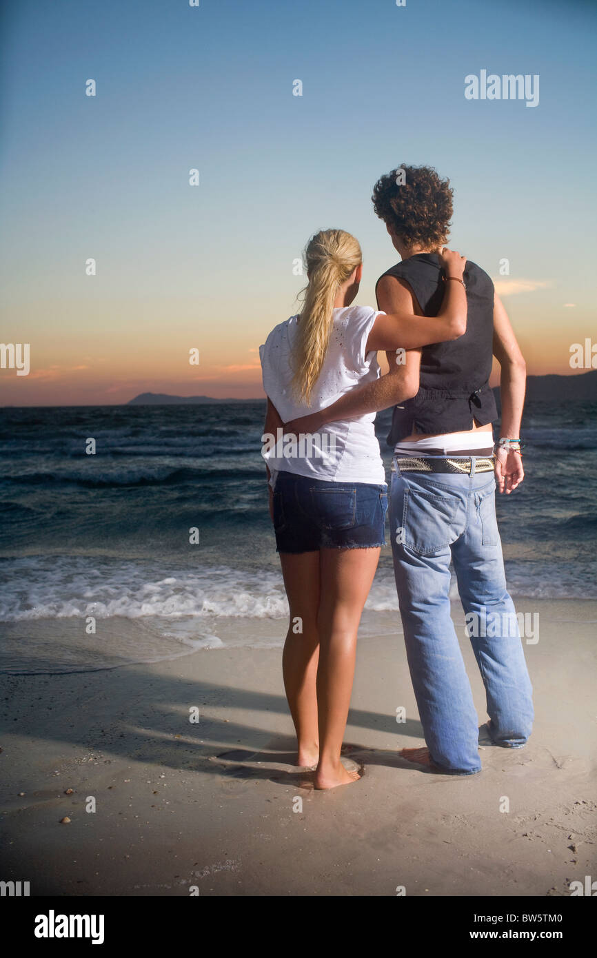 Loving cple look out to sea sunset - Stock Image