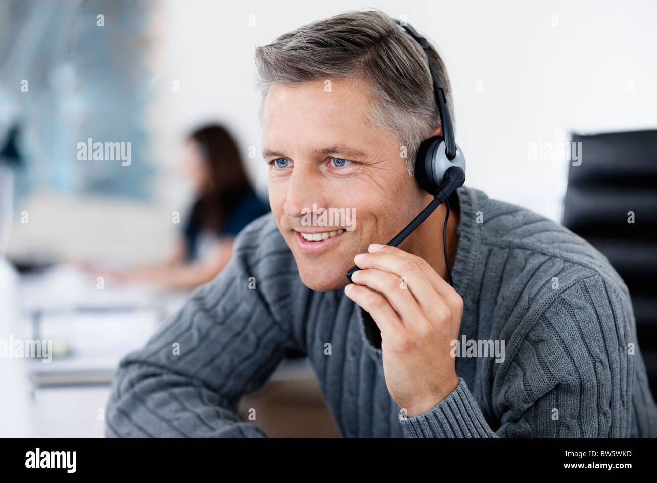 Businessman phoning with headset - Stock Image
