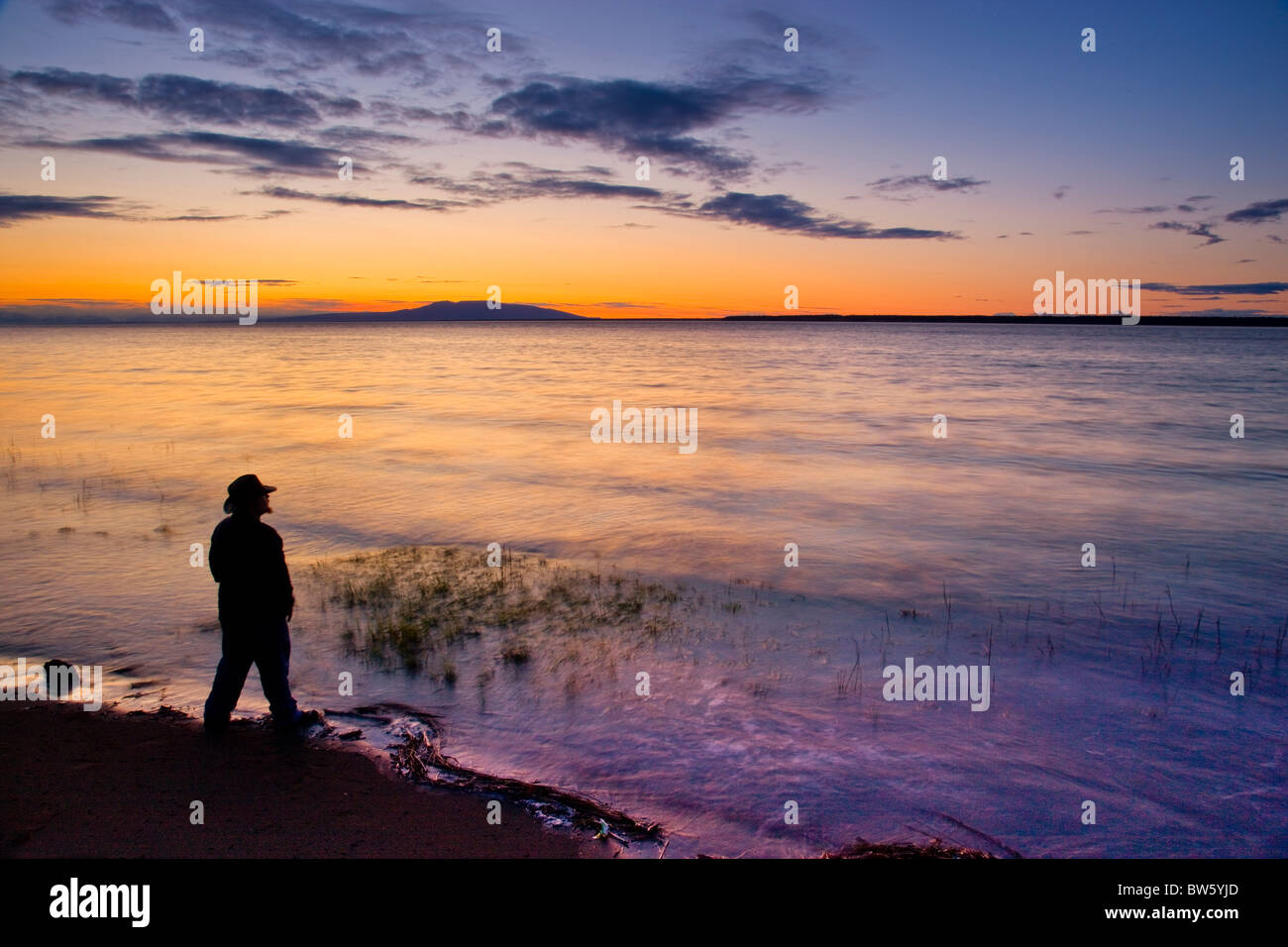 Silhouette of a man standing on the shore of Knik Arm while watching  the sunset over Mount Susitna, Alaska, Summer Stock Photo