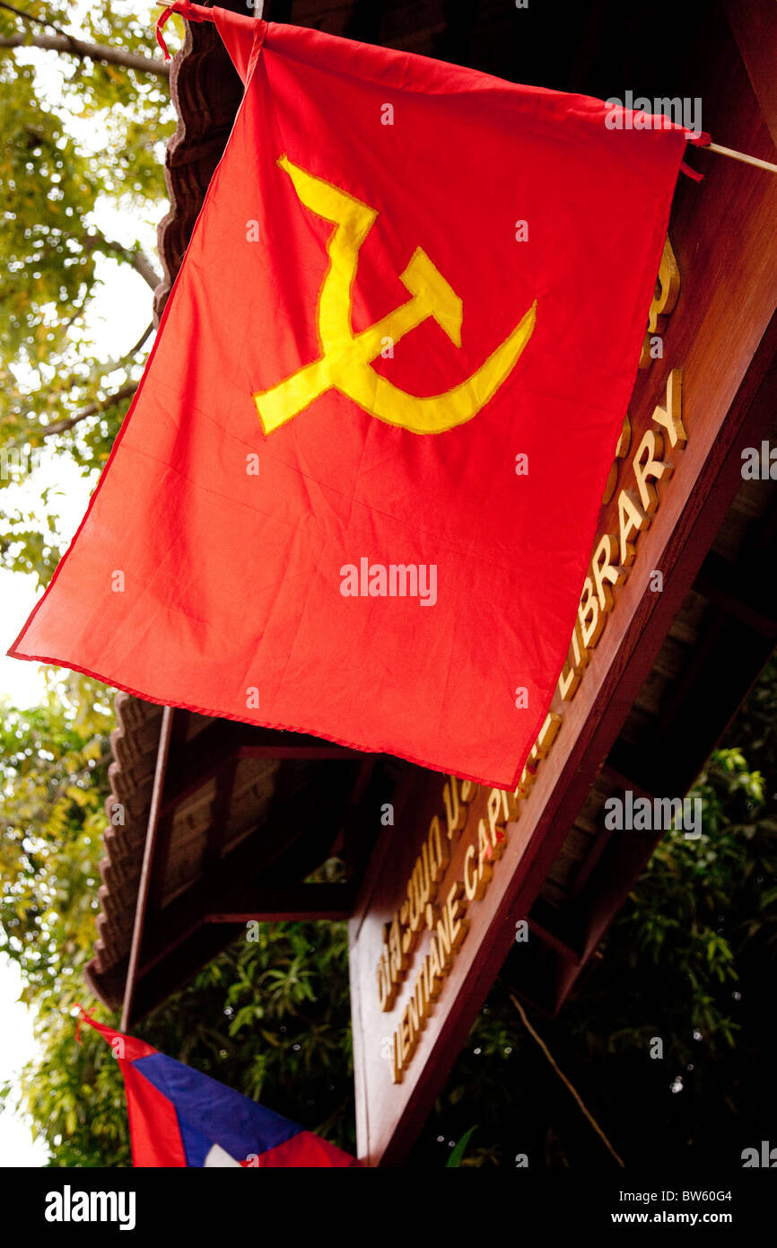 The hammer and sickle flag of communism flies at the gate of Vientiane's library on Lane Xiang Avenue - Stock Image