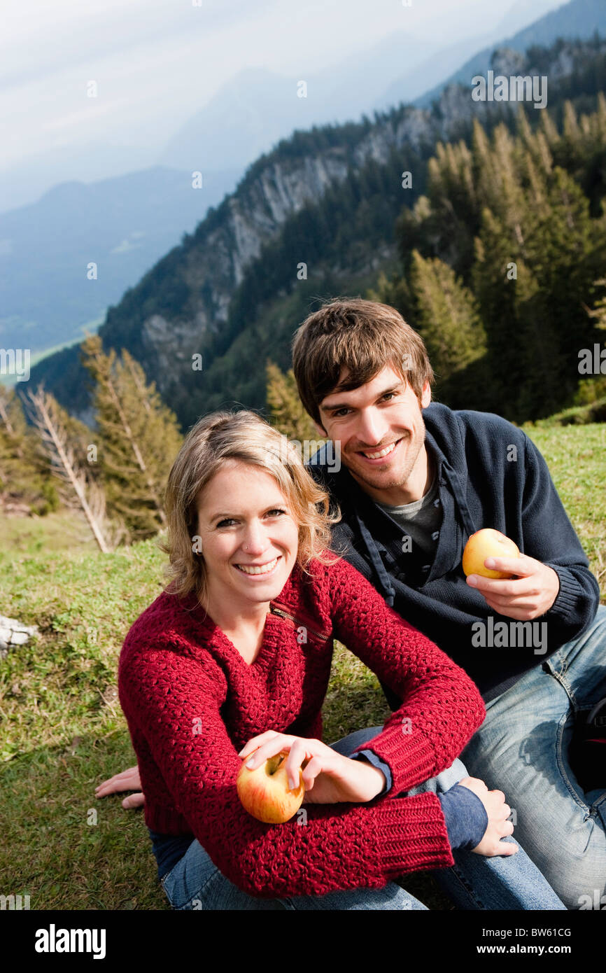 Couple eating apples while resting - Stock Image