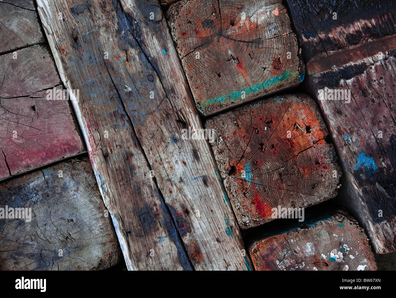 Rough cross cut timber stained with paint and wood stain in a shipyard where it's been stained with paint over - Stock Image