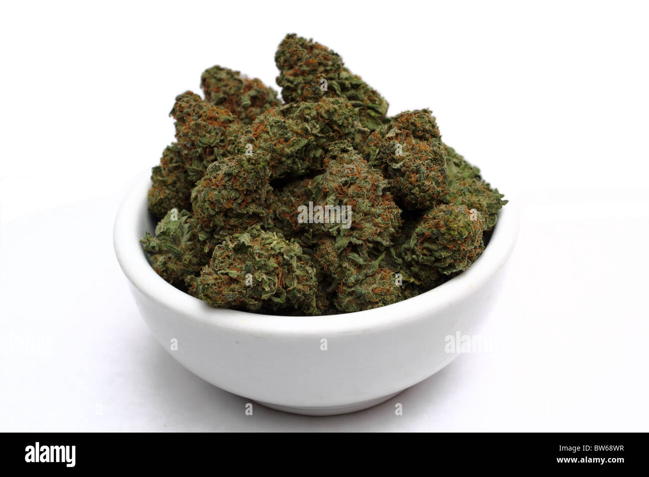 Marijuana ( Cannabis ) Bud up close showing detailed trichomes and red hairs on isolated white background in white - Stock Image
