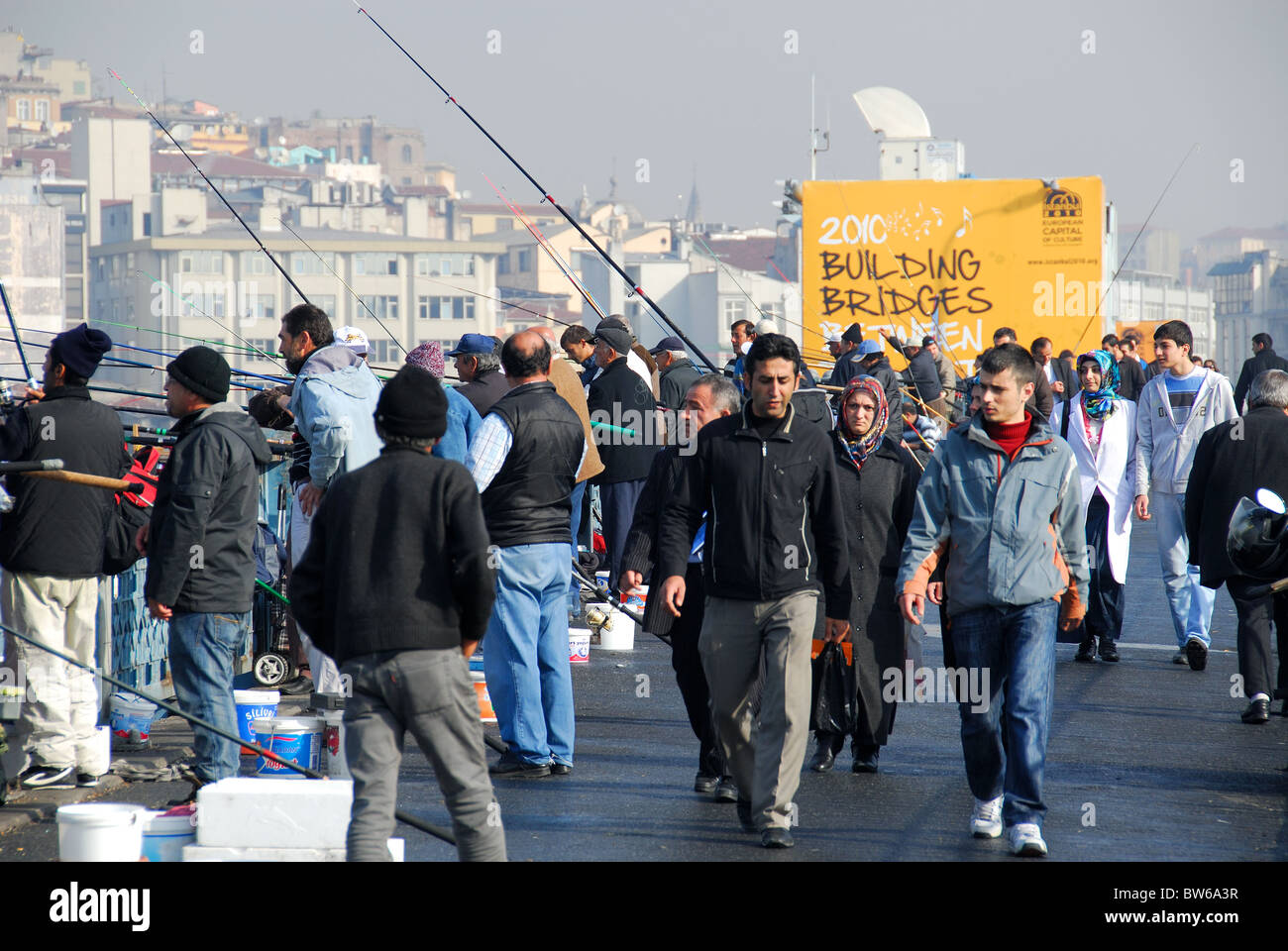 ISTANBUL, TURKEY. People walking over, and fishing from, the Galata Bridge, with Karakoy district in the background. Stock Photo