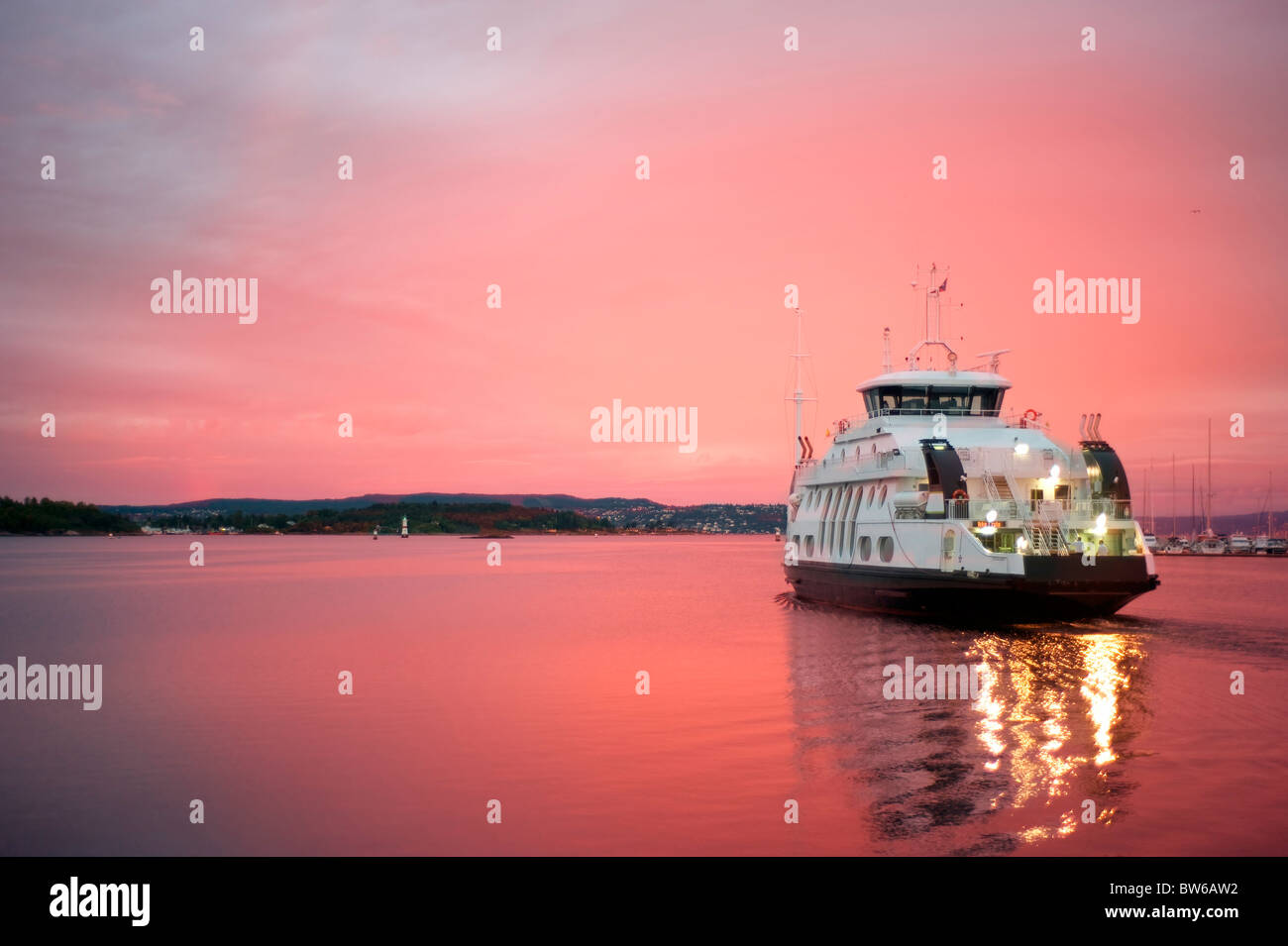 Cruise liner floating away from the Olso harbor at dawn - Stock Image