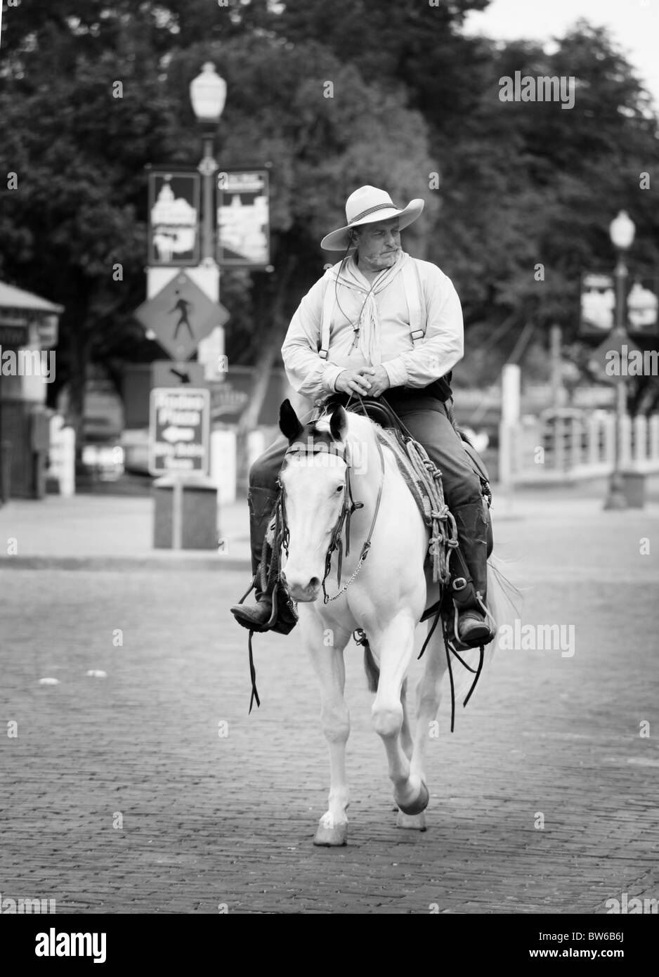 Cowboy riding through the Stock Yards at Fort Worth, Texas - Stock Image