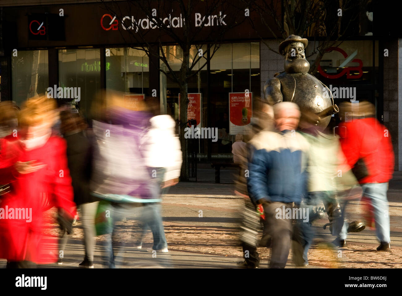 Desperate Dan towering over blurred passing shoppers on a sunny day in Dundee,UK Stock Photo