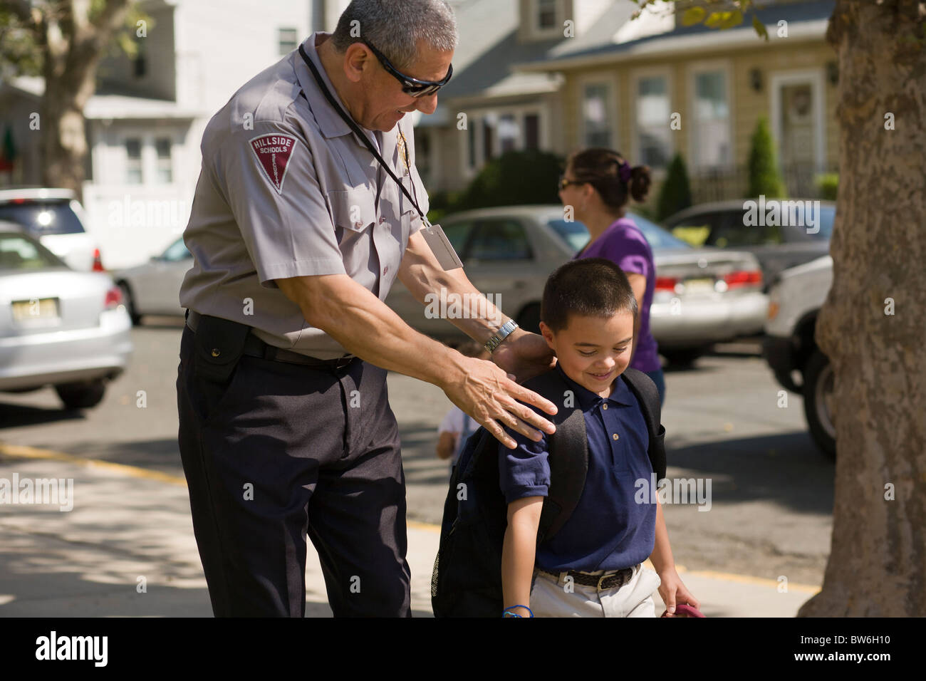 School security guard talking with a student after school - Stock Image
