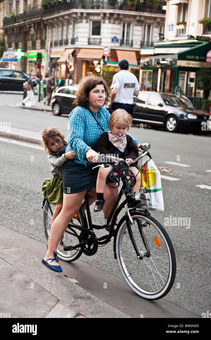 sturdy young mother with two small daughters clinging to her bicycle prepares to pedal off along Boulevard Saint - Stock Image