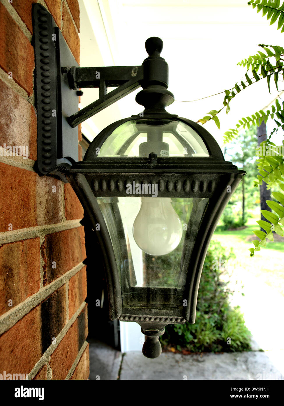 Outdoor Residential Light Fixture With White Bulb In A Metal Black Antique Frame On Red Brick Wall Bracket Glass House