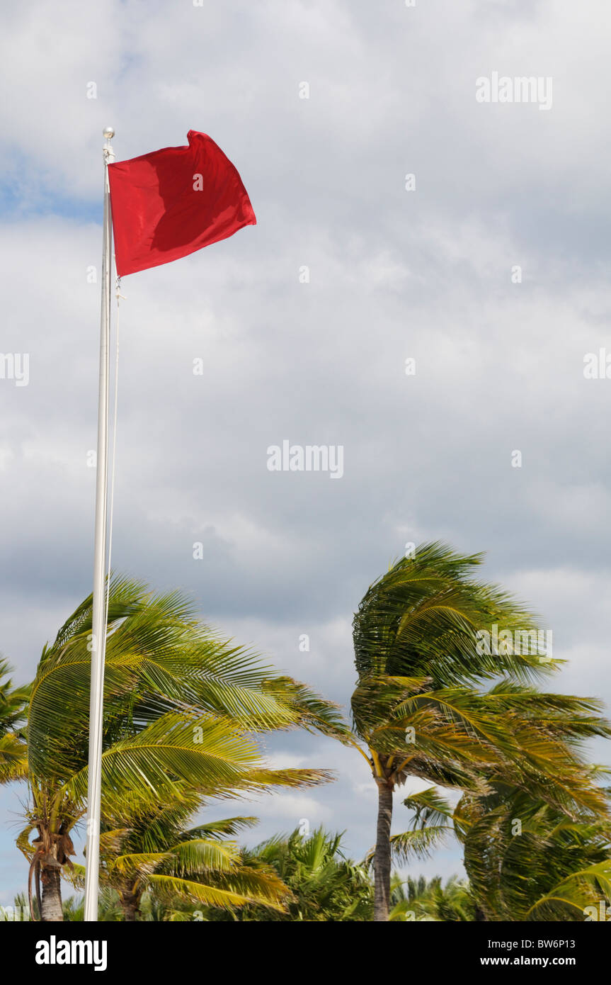 Red caution flag at a Caribbean beach during high winds from the approaching Hurricane Tomas - Stock Image