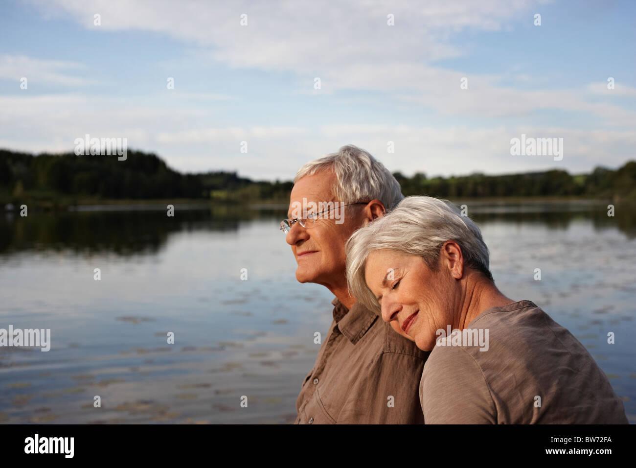 Senior woman lying head on mans shoulder Stock Photo