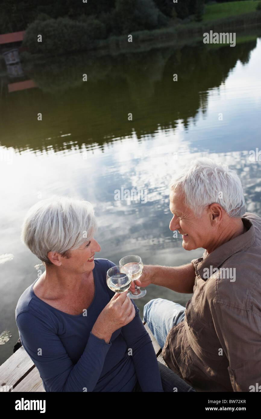 Senior couple clinking glasses of wine - Stock Image