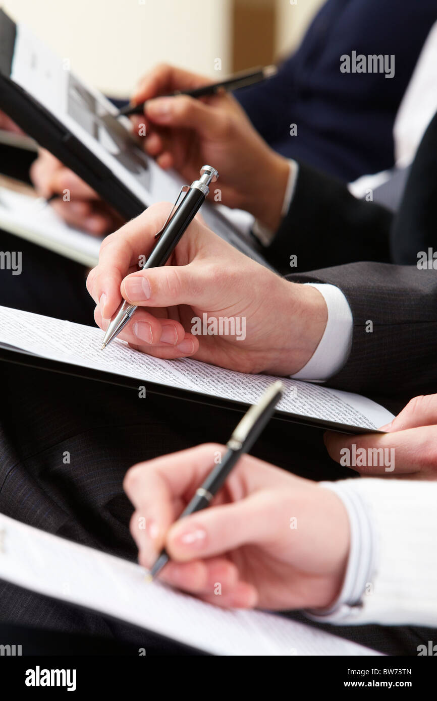 Close-up of business person hand with documents writing at lecture - Stock Image
